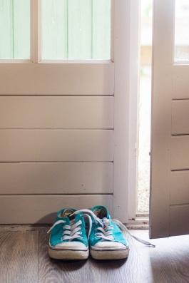 blue sneakers by open door